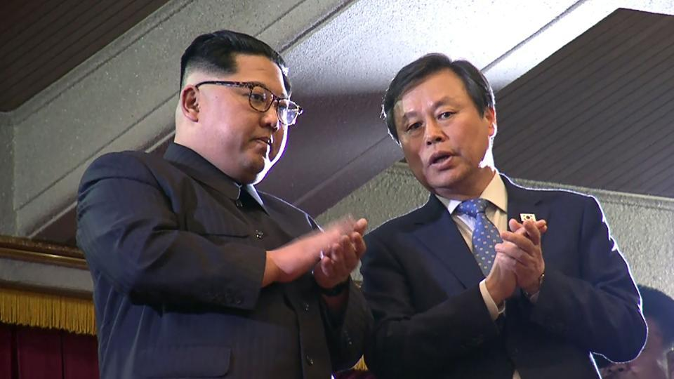 This picture captured from a video footage by Korea Pool reporters shows North Korean leader Kim Jong Un (left) and South Korea's culture minister Do Jong-whan (R) during a rare concert by South Korean musicians at the 1,500-seat East Pyongyang Grand Theatre in Pyongyang.