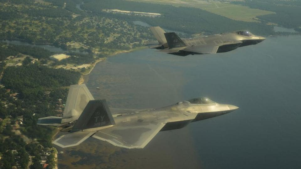 An F-22A Raptor, foreground, and an F-35A Lightning II joint strike fighter fly over Florida's Gulf coast in 2012.