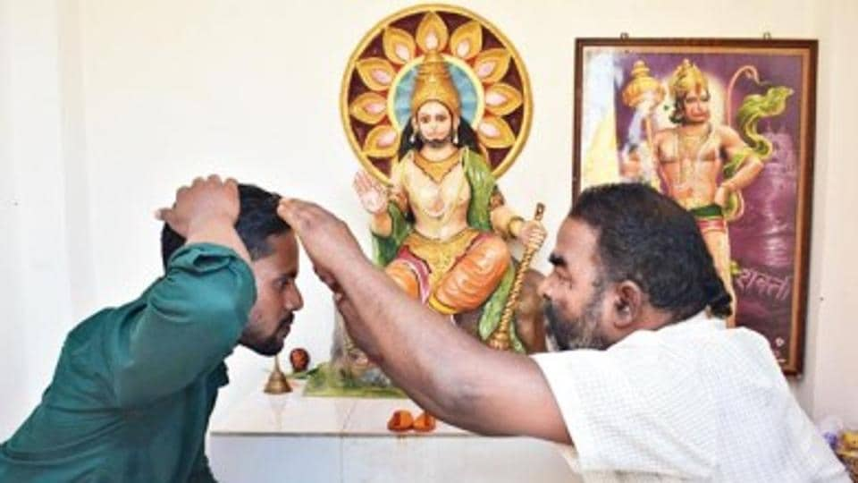 Mohammad Pappu (left) being blessed by the priest of the temple he repaired with his paltry income.