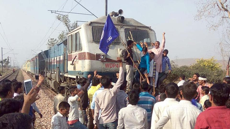 Protesters stop a train at Ghatla railway station in Alwar district on Monday .