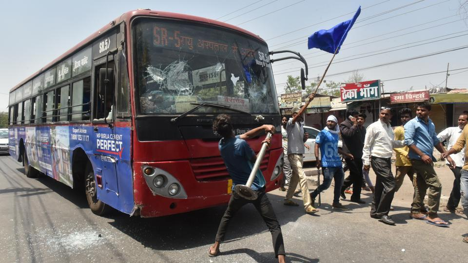 A protester vandalises a public bus during a demonstration by Dalit organisations as part of a countrywide strike against the Supreme Court's order of diluting the Scheduled Castes and Scheduled Tribes (Prevention of Atrocities) Act, in Bhopal, Madhya Pradesh. 5 people have been killed during violence in the state with another person killed in Rajasthan. (Mujeeb Faruqui/HT Photo)
