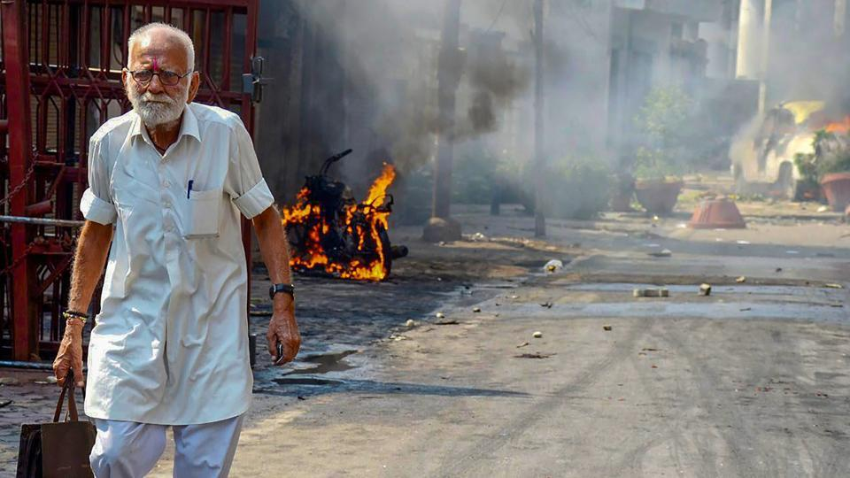 Protestors hurl brickbats as smoke billows from burning cars during Bharat Bandh over the alleged dilution of Scheduled Castes/Scheduled Tribes Act in Muzzaffarnagar in Uttar Pradesh on Monday.