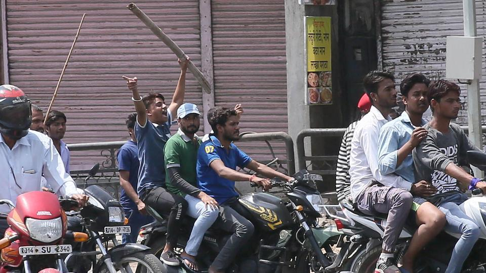Protesters brandish sticks as they cross closed shops during a bandh in Jaipur on Monday.