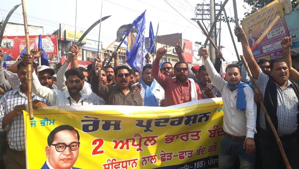 Protesters brandishing swords during the Bharat bandh protest in Hoshiarpur on Monday. (HT Photo)