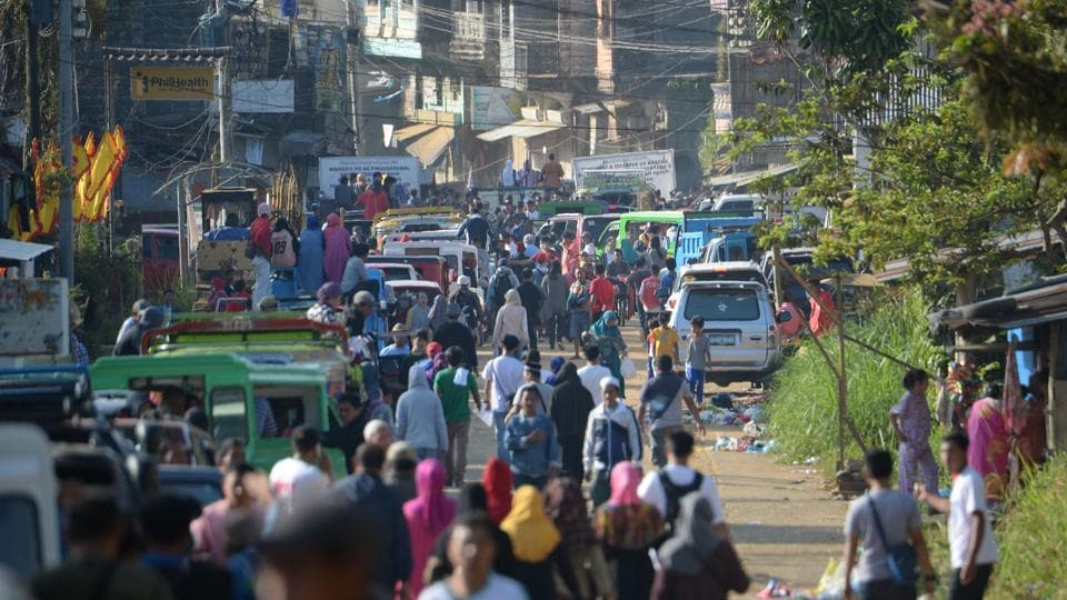 Thousands of residents wait to pass through a military check point to visit their destroyed houses at the main battle area in Marawi City. Over the course of the next month other groups of residents will be allowed to return for up to three days each, to view their old homes and salvage what they can before rebuilding starts. (Ted Aljibe / AFP)