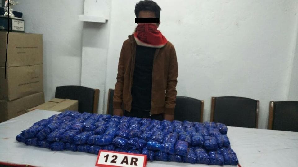A drug smuggler stands in front of the seized drug consignment, displayed in an office of the 12 Assam Rifles in Imphal on Monday.