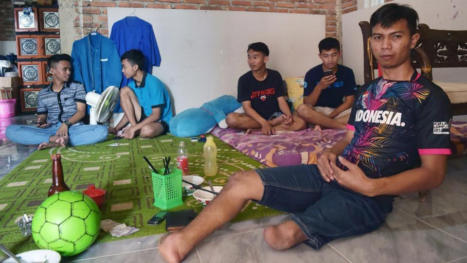"When Eman Sulaeman (R) begged his parents as a child to let him play football, the couple worried their son -- born with no feet and just one full leg -- would be mocked. ""I cried for days, begging them to buy me a ball,"" he said, in the small town of Indramayu, 220 kilometres east of Jakarta. ""They relented and went out to find me a cheap plastic ball."" (Adek Berry / AFP)"