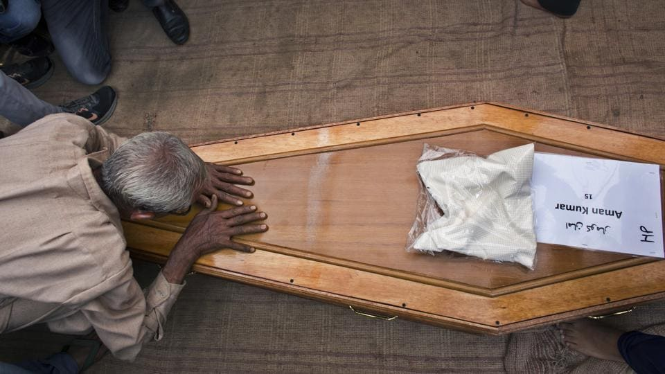 A relative pays his respects to the casket containing the remains of Aman Kumar, who was among the Indian construction workers killed by the Islamic State in Iraq, on April 3, 2018 in Dharmsala, Himachal Pradesh. Prime Minister Narendra Modi on Tuesday announced an ex-gratia of Rs 10 lakh for each of the families of 39 workers killed in Iraq. (Ashwini Bhatia / AP)