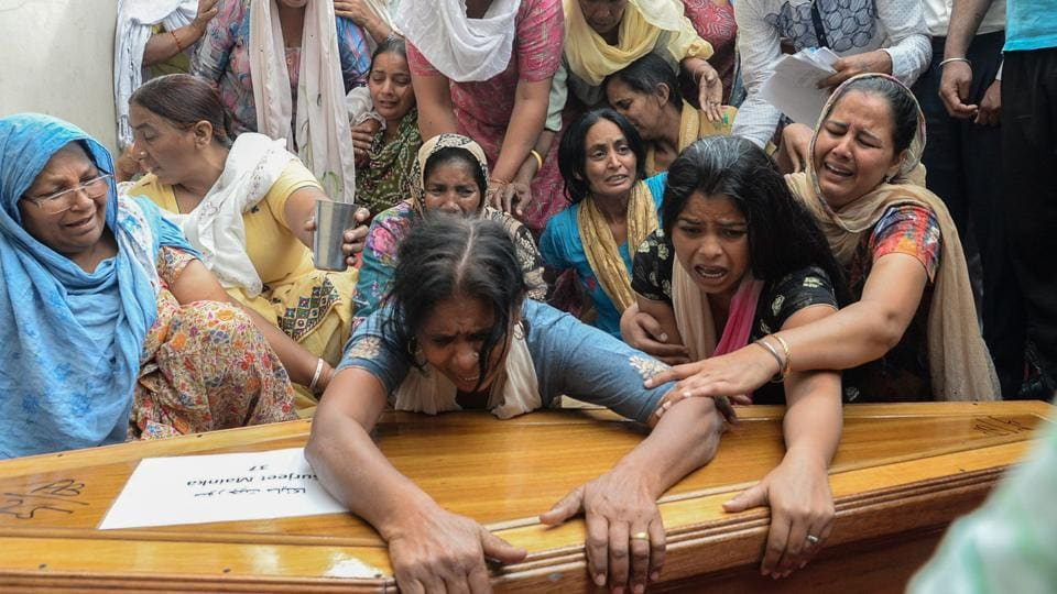 Relatives of construction worker Surjeet Mainka, who was killed in Iraq, grieves over his coffin in Chuhar Wali village on the outskirts of Jalandhar on April 3, 2018.