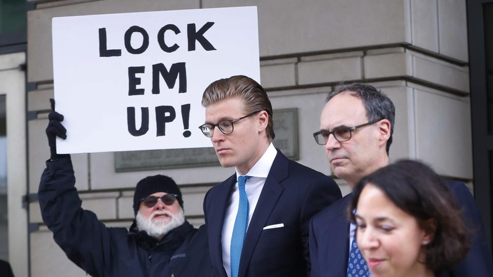 Alex van der Zwaan leaves Federal District Court in Washington, Tuesday, April 3, 2018. Holding the sign up is Bill Christeson from the Washington area.