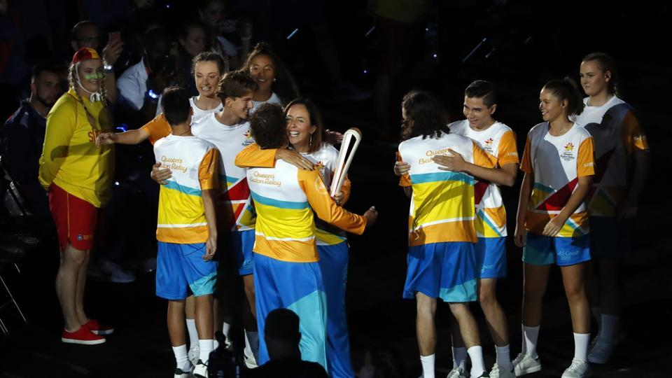 Liz Ellis passes the baton to Brent Livermore during the opening ceremony. (REUTERS)