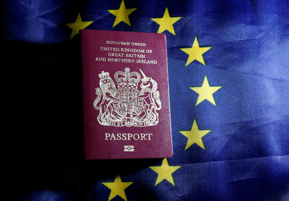 A British passport is pictured in front of a European Union flag.