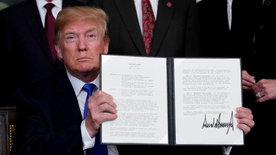 US President Donald Trump holds his signed memorandum on intellectual property tariffs on high-tech goods from China, at the White House in Washington on March 22, 2018.