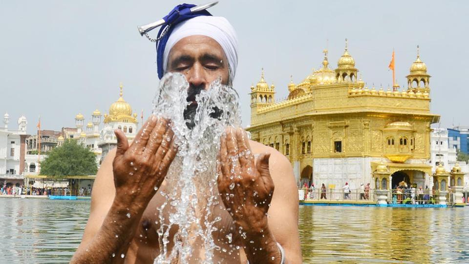 A devotee takes a dip in the holy sarovar on the birth anniversary of Guru Teg Bahadur at the Golden Temple in Amritsar on Thursday. (Sameer Sehgal/HT)