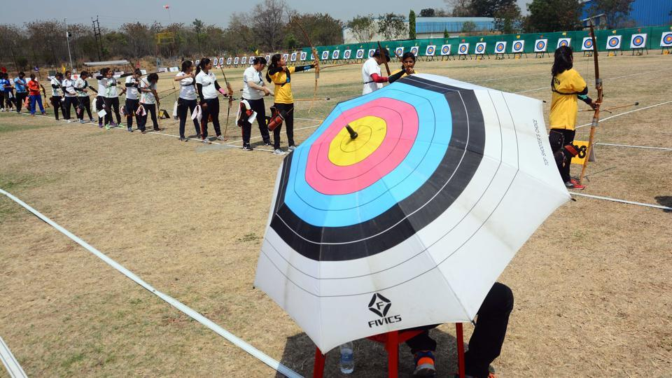 A referee is seen using an umbrella which is a replica of an archery board as participants from various states compete. (Shankar Narayan/HT PHOTO)