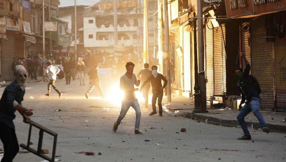 Kashmiri students throw stones at policemen as a tear gas shell explodes behind them during a protest in Srinagar on Thursday.