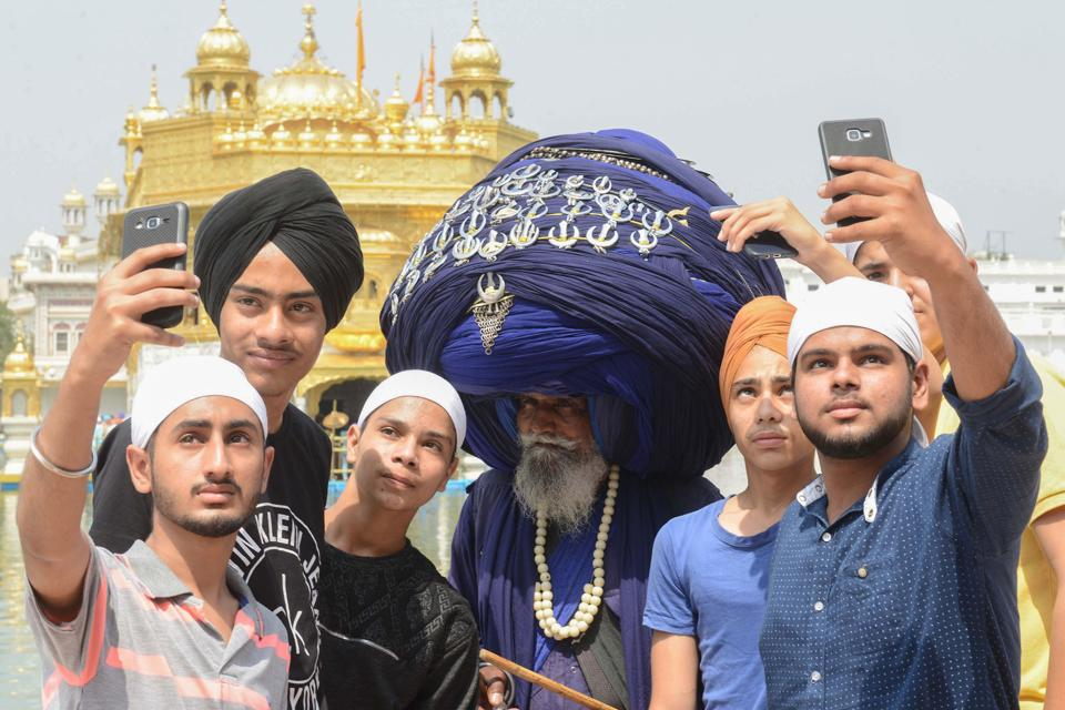 Visitors take a selfie with a Nihang (traditional Sikh religious warrior) Baba Jagir Singh wearing a giant turban at the Golden Temple in Amritsar. (AFP)