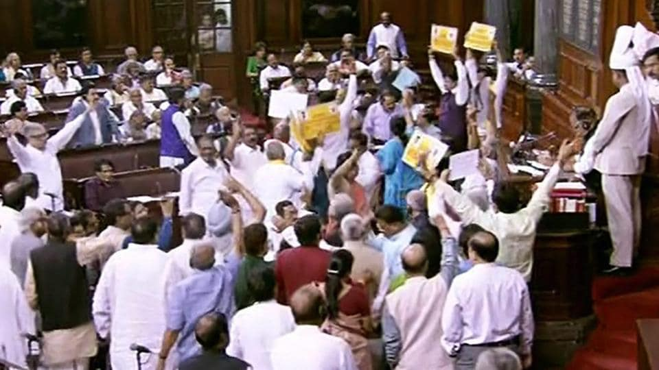 Opposition members protest during the on-going budget session of Rajya Sabha, at Parliament House in New Delhi on Wednesday.