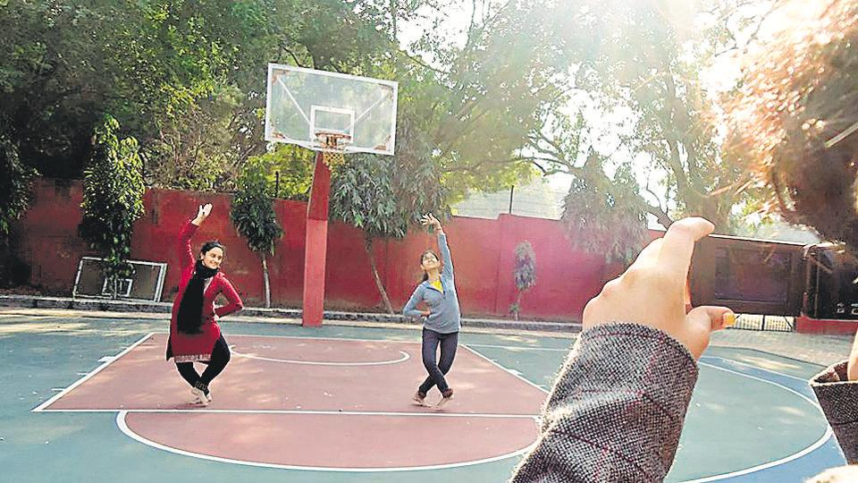Aishwarya Kali records while Swathi Gangadharan and Tirna Sengupta perform on a basketball court.