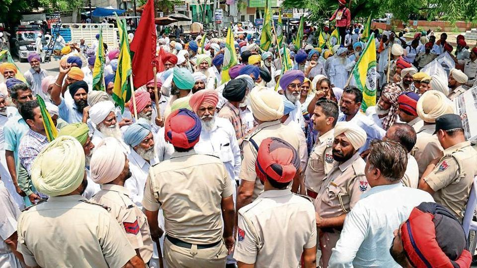 """Policemen stop farmers during a protest march in Bathinda. Faced with mounting criticism, chief minister Amarinder Singh recently announced in the assembly that the government will """"waive farm loans amounting to ₹9,500 crore within the upcoming financial year 2018-19""""."""