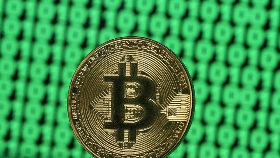 A token of the virtual currency Bitcoin is seen placed on a monitor that displays binary digits in this illustration picture.