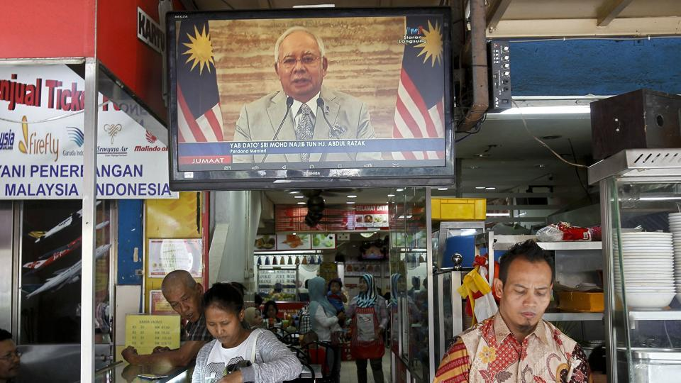 Passerby walks in front of a live broadcast of an announcement by Malaysian Prime Minister Najib Razak at a restaurant in Kuala Lumpur, Malaysia, on April 6, 2018.