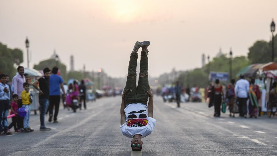 Passers-by look on as Mohammed Al Hendi does a headstand at Raj Path. The group found regional fame with its appearances on Arabs Got Talent, a variant of the American talent reality show and is now based out of Jordan after difficulties with Palestinian border closures made representing their country in parkour and free running tournaments difficult. (Burhaan Kinu / HT Photo)