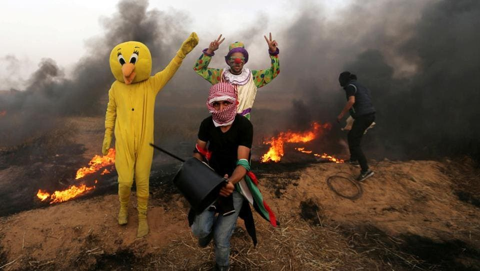 Palestinians wearing costumes are seen at the site of clashes along the Israel-Gaza border in the southern Gaza Strip. (Ibraheem Abu Mustafa / REUTERS)