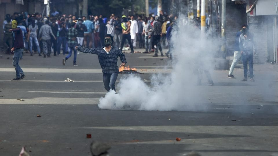 People throw stones at security forces during a protest against the recent Shopian killings, in Srinagar on Friday.