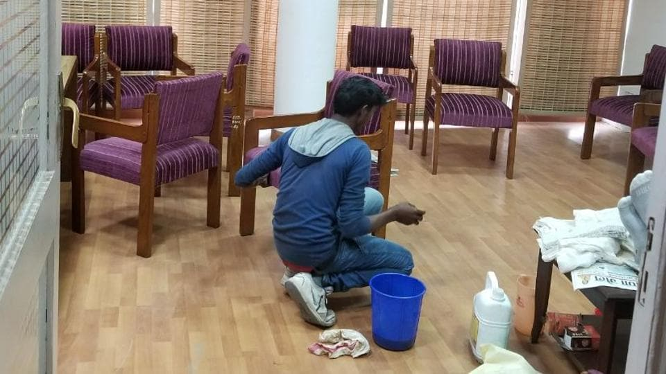 A worker polishing furniture in room number 19 on the seventh floor of the secretariat.