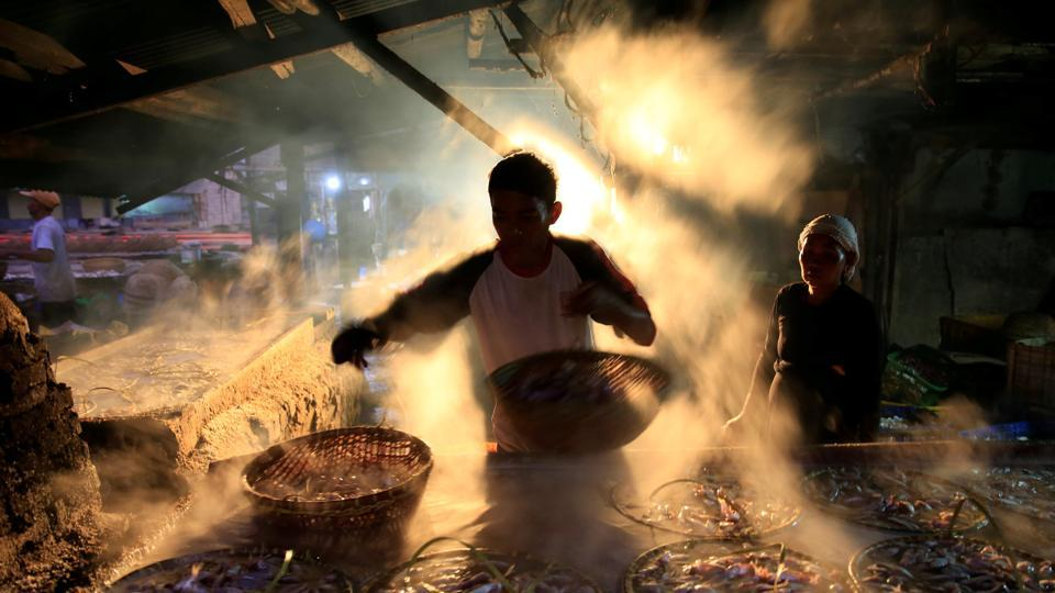 A street vendor is seen marinating fish at Cilincing district in Jakarta, Indonesia. (Beawiharta / REUTERS)
