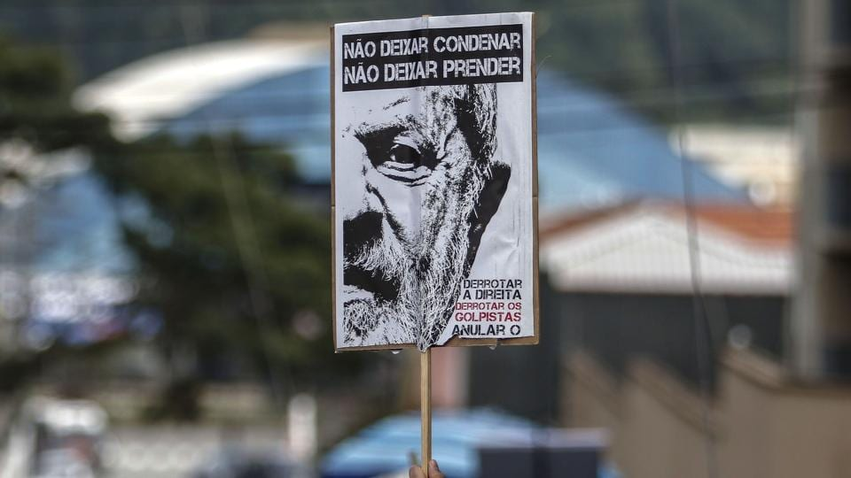 A supporter of Brazilian former president Luiz Inacio Lula da Silva holds a sign with his image during a Catholic Mass in memory of Lula's late wife Marisa Leticia in the Metallurgical Union, in Sao Bernardo do Campo, Brazil, after judge Sergio Moro issued a warrant to send Lula to prison, on April 7, 2018.