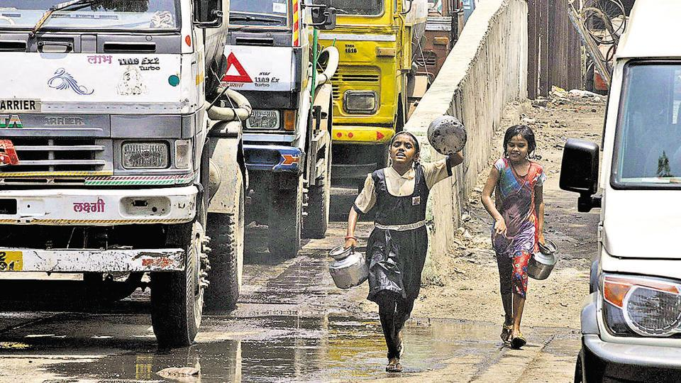 Children run behind water tankers at a water supply depot near Parvati. Parts of the city have been facing acute water shortage, bringing to light the issue of water scarcity which is rising due to rapid urbanisation. (HT PHOTO)