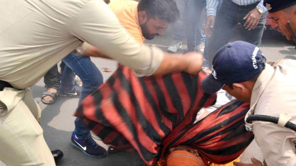 Police personnel try to douse flames after  VHP district coordinator Charanjeet Pahwa attempted self-immolation in Jwalapur in Haridwar on Sunday.