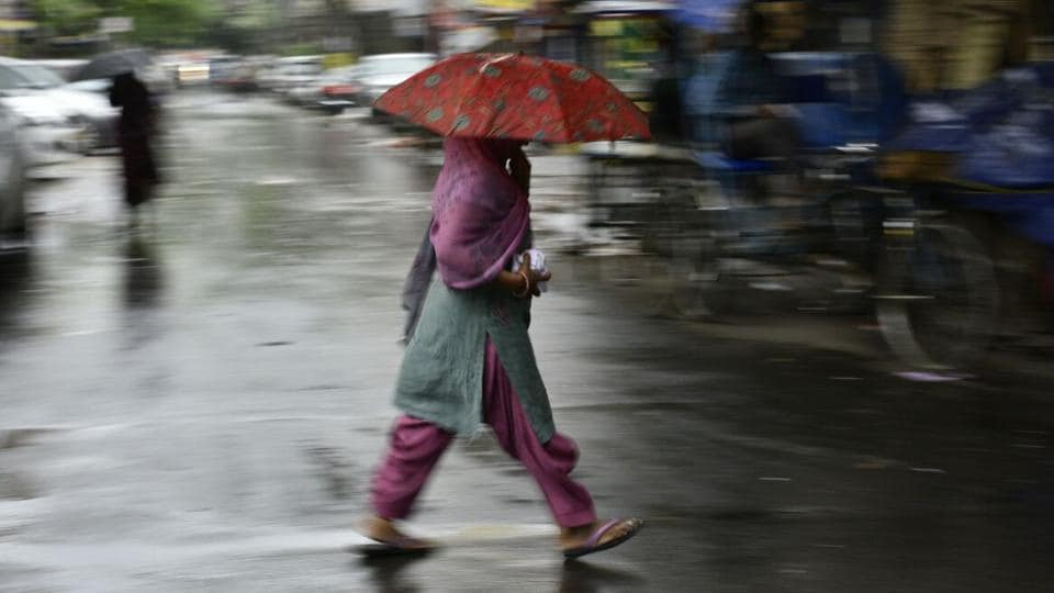 A woman walks in the rain under an umbrella through the lanes of Jangpura. Delhi woke up to a light downpour preceded by a thunderstorm on Monday morning, with the temperature dipping to 24 degree Celsius. (Anushree Fadnavis / HT Photo)