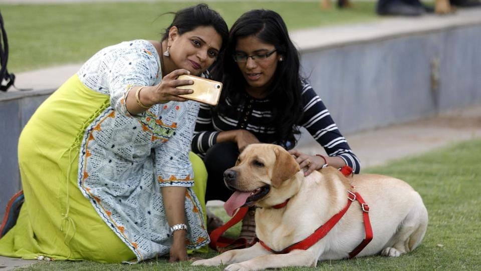 Visitors at the PetYo festival taking a selfie with a labrador at Amanora Club House in Pune on April 8.  (RAHUL RAUT/HT PHOTO)