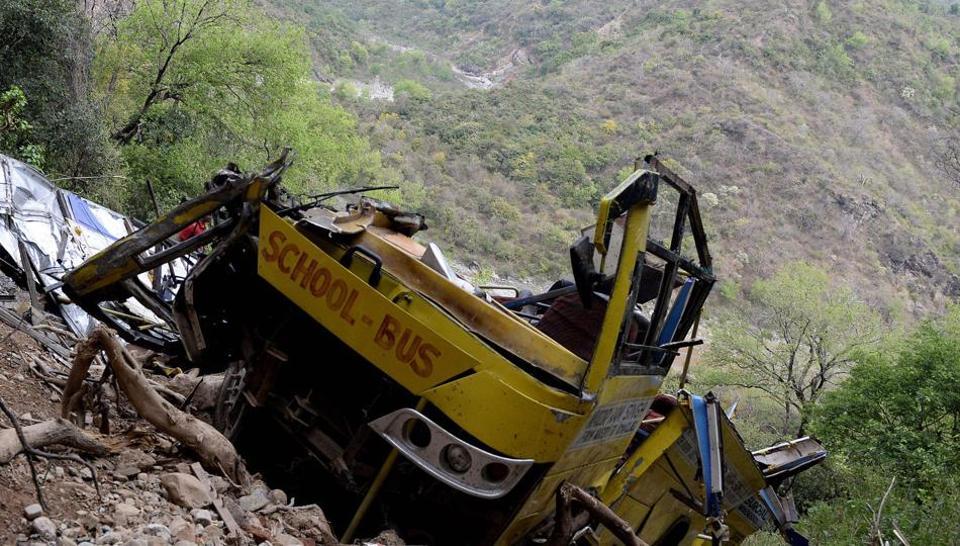 Indian villagers look at a wrecked school bus near Nurpur in Kangra district, Himachal Pradesh, April 10, 2018