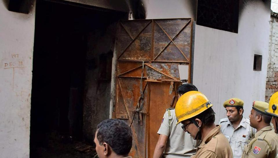Delhi Fire Service personnel inspect the building of Raja Park factory where a major fire broke out around 6.35 am, in Sultanpuri, New Delhi on Monday.