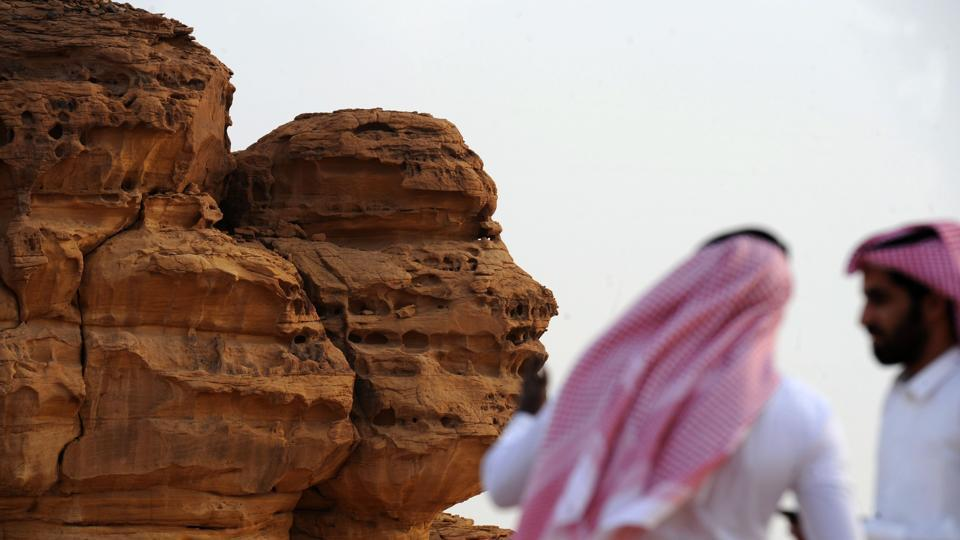 A picture taken on March 31, 2018 shows Saudi men visiting the Khuraiba archaeological site near Saudi Arabia's northwestern town of al-Ula. Al-Ula, an area rich in archaeological remnants, is seen as a jewel in the crown of future Saudi attractions as the austere kingdom prepares to issue tourist visas for the first time.