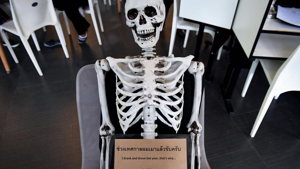 A skeleton on a chair warns against drinking and driving at the Kid Mai Death Awareness Cafe in Bangkok, Thailand. With drinks called 'Death' and 'Painful' on the menu and a skeleton splayed out in the corner, the meet-your-maker theme is alive and well at this open-air lunch spot in the Thai capital. (Lillian Suwanrumpha / AFP)