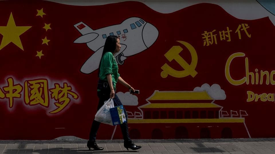 A woman passes a wall mural which reads 'China Dream' in Shanghai on April 11, 2018.