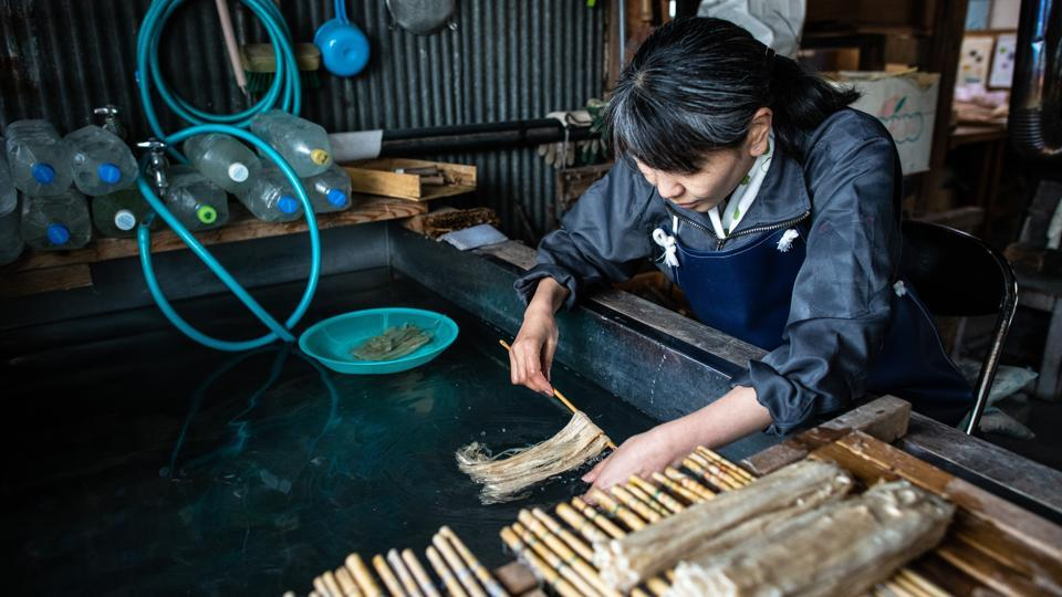 Karumi Nakano runs the now soft and pliant kozo fibers in pure running water one last time to remove lye residue and untangle individual fibers as they near the stage of becoming paper. Any minerals or impurities in the water at this stage can ruin the paper quality. (Carl Court / Getty Images)