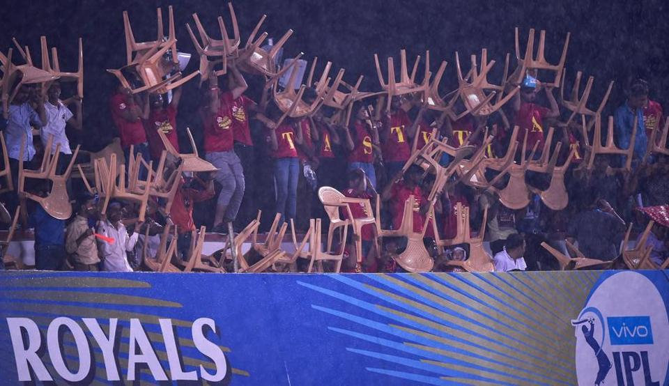 Spectators use plastic chairs to protect themselves from the rain during the 2018 Indian Premier League (IPL 2018) Twenty20 cricket match between Rajasthan Royals and Delhi Daredevils at the Sawai Mansingh Stadium in Jaipur on Wednesday