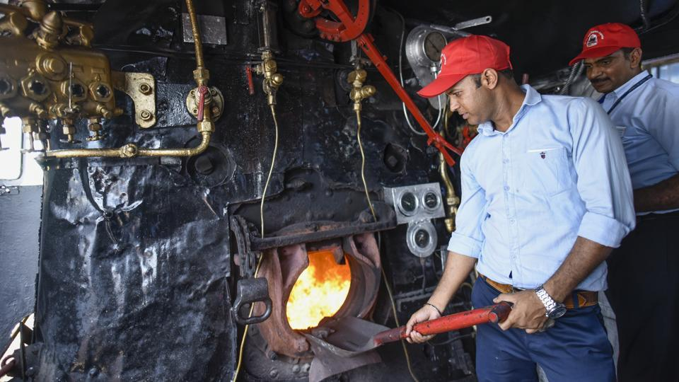 A railway worker shovels coal into the grate. Azad was brought to India from Baldwin, Philadelphia in 1947. The giant yesteryear's engine has a capacity to hold around 25,000 litre of water and 15 tonnes of coal and can run at a speed of 100 kmph. (Burhaan Kinu / HT Photo)