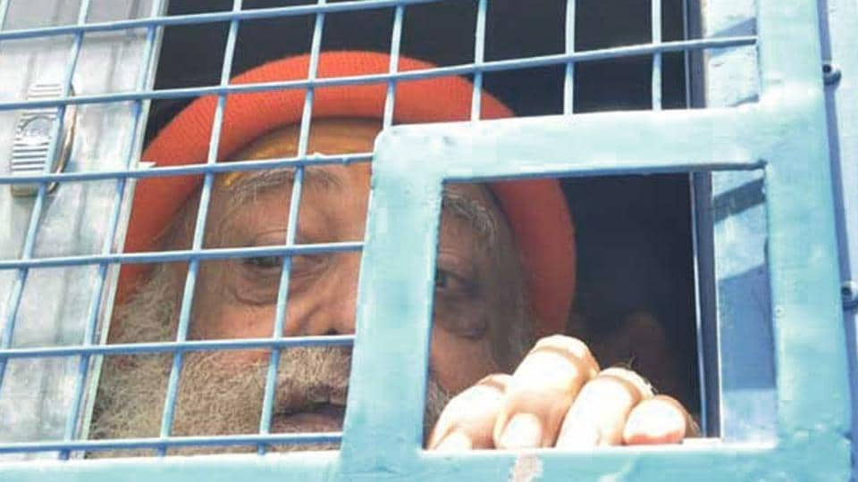 Asaram looks out from the police van while on way to attend the hearing in a court in Jodhpur.