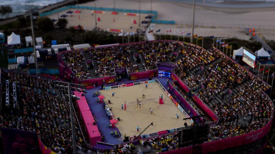A tilt and shift image shows Ben O'dea and Sam O'dea of New Zealand (top) competing against Samuel Pedlow and Sam Schachter of Canada during their men's beach volleyball semi-final match at the Coolangatta beachfront on April 11, 2018. (Manan Vatsyayana / AFP)