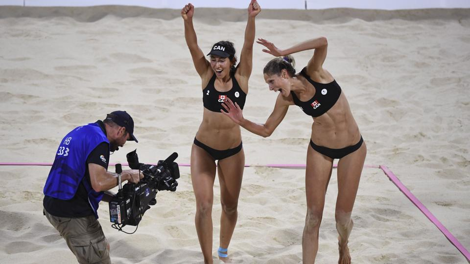 Canada's Melissa Humana-Paredes (C) and Sarah Pavan (R) celebrate winning the gold medal in the women's beach volleyball final against Australia on April 12, 2018. (William West / AFP)