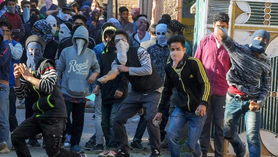 Youth throw stones at police during clashes with security forces on Thursday following a protest over the deaths of civilians at Kulgam in Jammu and Kashmir.