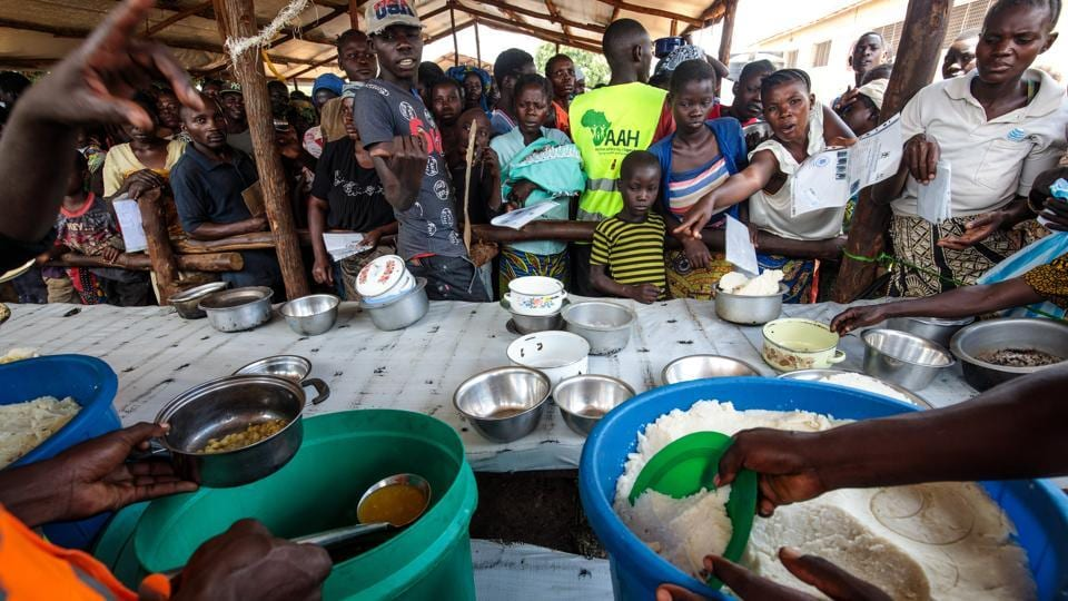 Refugees from the DRC are given a lunch consisting of maize and peas from the World Food Programme by volunteers in the Kyangwali settlement. The World Food Programme anticipates providing food and nutrition for up to 1.6 million refugees this year. (Jack Taylor / Getty Images)
