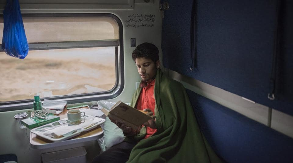 A passenger sits reading a book in his cabin while travelling the Green Line train service from Karachi to Islamabad.